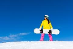 Сноуборд владением положения девушки Snowboarder, снег стоковое фото
