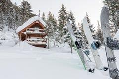 Сноуборд на шале дома в лесе зимы с снегом в mountai Стоковые Фотографии RF