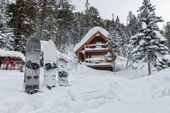 Сноуборд на шале дома в лесе зимы с снегом в mountai Стоковое Фото