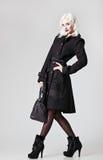 Снятая мода студии: красивая девушка в черных пальто и ботинках, с сумкой в руке стоковое фото