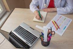 Снятый женских рук ` s врача Таблица деятельности ` s доктора медицины Стоковые Изображения