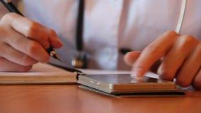 Снятый женских рук ` s доктора используя умный телефон Профессионал перечисляющ и ищущ информацию видеоматериал