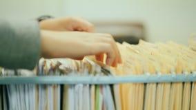 Снятый конец-вверх: женщина раскрывает ящик, смотрит примечания Работа с помещенными в архив документами акции видеоматериалы