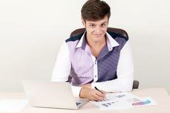 Снятый красивого творческого бизнесмена директора работая в офисе пока сидящ на столе с компьтер-книжкой Стоковое Изображение