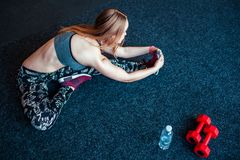 Снятый молодой женщины протягивая на спортзале Мышечная женщина делая тренировки для того чтобы протянуть ее тело на поле Стоковое Изображение RF