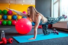 Снятый молодой женщины протягивая на спортзале Мышечная женщина делая тренировки для того чтобы протянуть ее тело на поле Стоковые Изображения