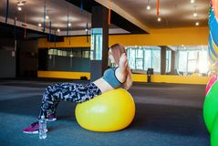 Снятый молодой женщины работая на спортзале Мышечная женская тренировка используя шарик делать сидит поднимает женщину стоковая фотография