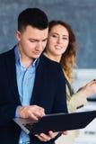 Снятый молодого бизнесмена работая на компьтер-книжке с его партнером Стоковая Фотография