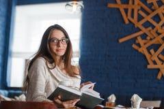 Снятый молодой стильной женщины используя цифровую таблетку в кофе кафа и большой книге ` S жизни хорошее Стоковые Изображения