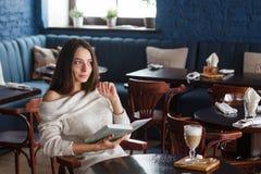 Снятый молодой стильной женщины используя цифровую таблетку в кофе кафа и большой книге ` S жизни хорошее Стоковые Изображения RF