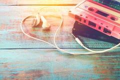 снятый ретро двухкатушечной кассеты с формой сердца наушника на деревянной таблице Стоковые Фотографии RF