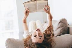 Снятый смешной женщины лежа на кресле с книгой Стоковое Изображение RF