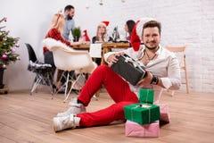 Снятый счастливых друзей наслаждаясь праздниками Сфокусируйте на человеке с подарочные коробки на переднем плане в красной шляпе  Стоковое Изображение