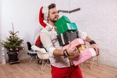 Снятый счастливых друзей наслаждаясь праздниками Сфокусируйте на человеке с подарочные коробки на переднем плане в красной шляпе  Стоковое фото RF