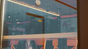 Снятый человека сидя в кафе с smartphone Снятый через окно выставки кафа сток-видео