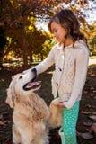 Собака давая свою лапку к маленькой девочке Стоковые Фото