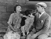 Собака в середине поцелуя пар (все показанные люди более длинные живущие и никакое имущество не существует Гарантии поставщика ко Стоковое фото RF