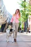 Собака женщины идя и говорить к друзьям на мобильном телефоне Стоковые Изображения RF