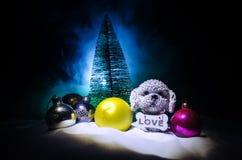 Собака игрушки - символ Нового Года под снегом на фоне ели разветвляет Собака игрушки как символ 2018 Новых Годов стоковое фото