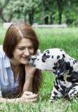 Собака идет расцеловать его предпринимателя -- молодая женщина Стоковые Фотографии RF
