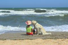 Собака молодой маленькой девочки и золотого Retriever сидя на пляже Девушка сидя самостоятельно с ее собакой стоковая фотография
