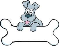 Собака мультфильма с лапками на знамени сформированном как косточка стоковые фото