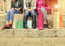 Соберите девушек сидя и беседуя после ходить по магазинам в городе Стоковое фото RF