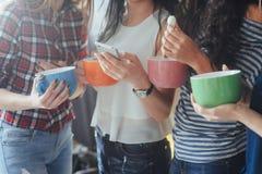 Соберите красивое молодые люди наслаждаясь в переговоре и выпивая кофе, девушках лучших другов совместно имея потеху, представляя стоковое изображение