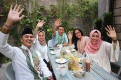 Соберите счастливых молодых мусульман развевая на таблице обедая во время ramadan c стоковая фотография rf