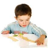 собирая головоломка мальчика Стоковое Изображение