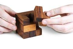 собирая кубик крупного плана руки укомплектовывает личным составом деревянное стоковые изображения