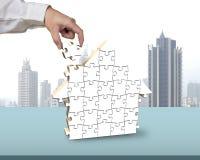 Собирая пустые белые головоломки в форме дома Стоковые Фотографии RF