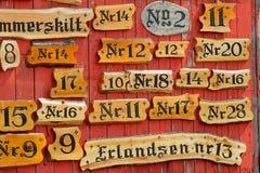 Собрание деревянных номеров дома против красного цвета покрасило стену Стоковая Фотография