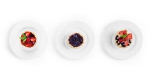 Собрание десертов с клубниками и смородинами на плите стоковые изображения