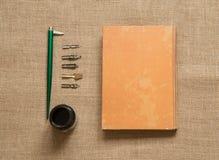Собрание канцелярские товара - ручки каллиграфии с чернилами на коричневом цвете стоковые фотографии rf