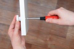Собрание мебели Руки конца девушки вверх Отвертка прикрепляет белую ручку к двери шкафа стоковое изображение rf