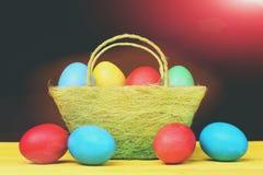 Собрание пасхи покрашенных декоративных яичек в зеленой корзине Стоковое фото RF