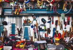 Собрание сортированных инструментов вися на стене со стендом работы стоковые фотографии rf