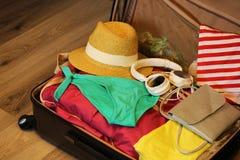 Собранный чемодан для перемещения Чемодан в открытом крупном плане взгляда с вещами в нейтральном положении на деревянной предпос Стоковая Фотография RF