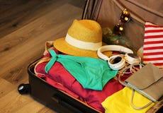 Собранный чемодан для перемещения Чемодан в открытом крупном плане взгляда с вещами в нейтральном положении на деревянной предпос Стоковые Изображения