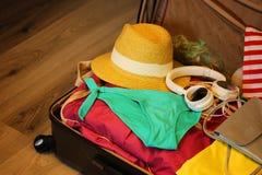 Собранный чемодан для перемещения Чемодан в открытом крупном плане взгляда с вещами в нейтральном положении на деревянной предпос Стоковые Фото