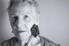 Собственная личность более старой женщины массажируя с малым massager Стоковые Изображения