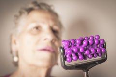 Собственная личность более старой женщины массажируя с малым massager Стоковое фото RF