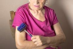 Собственная личность более старой женщины массажируя с малым massager Стоковая Фотография RF
