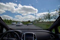 Собственная личность управляя автомобилем на занятой дороге с современной приборной панелью и чистым windscreen с новыми счищател стоковое фото