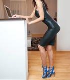 Совершенная женщина тела вкратце туго приспосабливать кожаное платье работая на компьтер-книжке в живущей комнате Взгляд со сторо Стоковые Фото