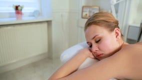 Совершенная релаксация в салоне курорта Молодая женщина в курорте расслабляющая массаж тайский сток-видео