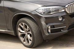 Совершенно новый автомобиль черноты SUV получает поцарапанный бампер автомобиля поврежденный в столкновении стоковые фотографии rf