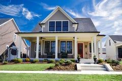 Совершенно новый изготовленный на заказ дом традиционного стиля с большим парадным крыльцом и красивым благоустраивать