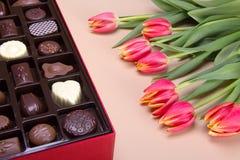 Совершенный сезонный подарок сортированного разнообразия шоколадов и цветков Стоковое Фото
